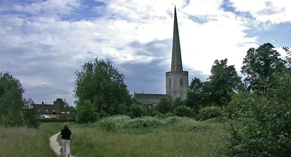 a path through a field with a church in the background