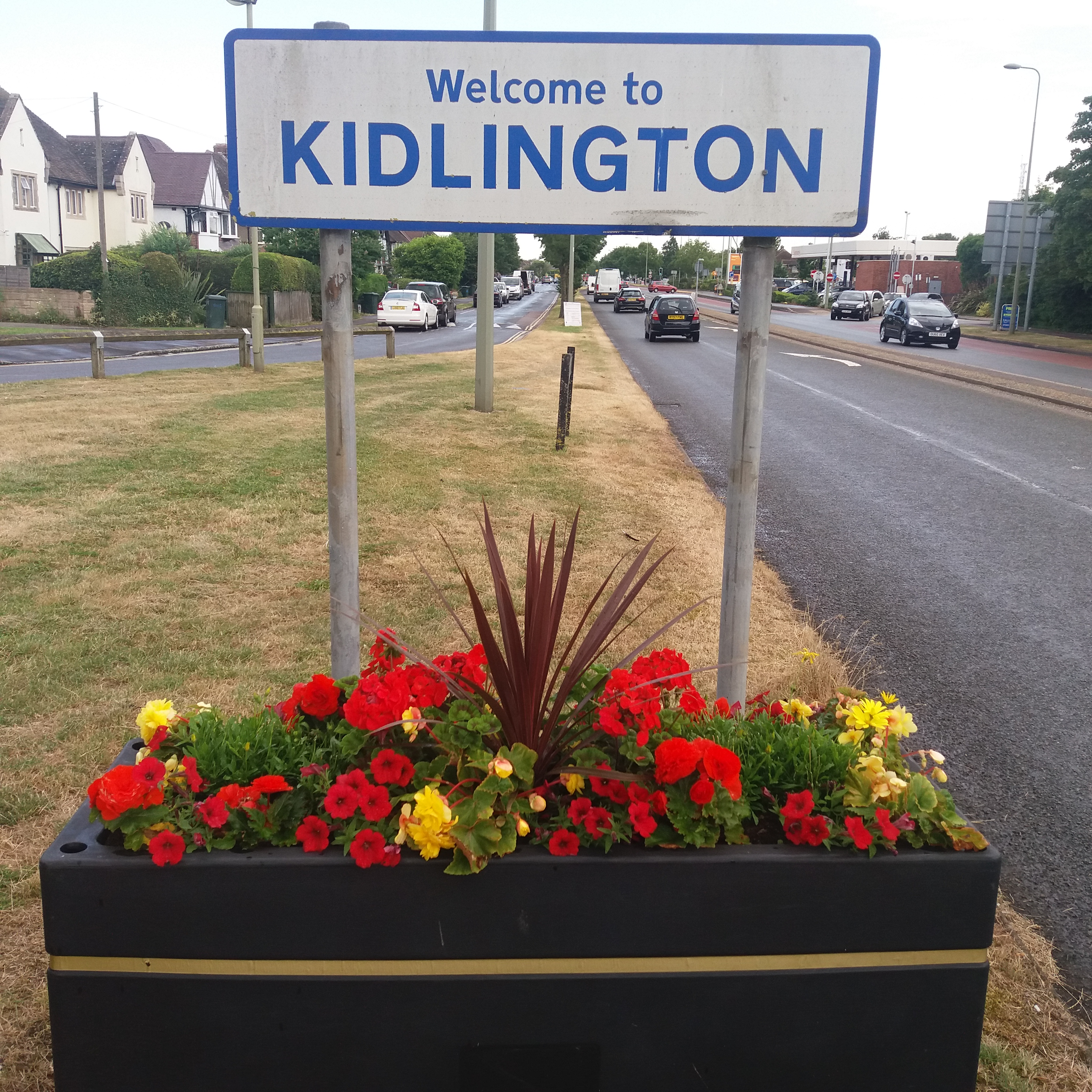 welcome to kidlington sign with flower baskets underneath